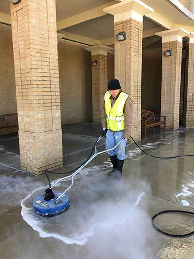 Image of Priority Exterior Cleaning, LLC. Employee Power Washing a commercial property sidewalk. Hospital and Hotel Pressure Washing Services